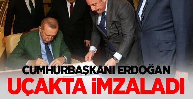 Cumhurbaşkanı Erdoğan uçakta imzaladı